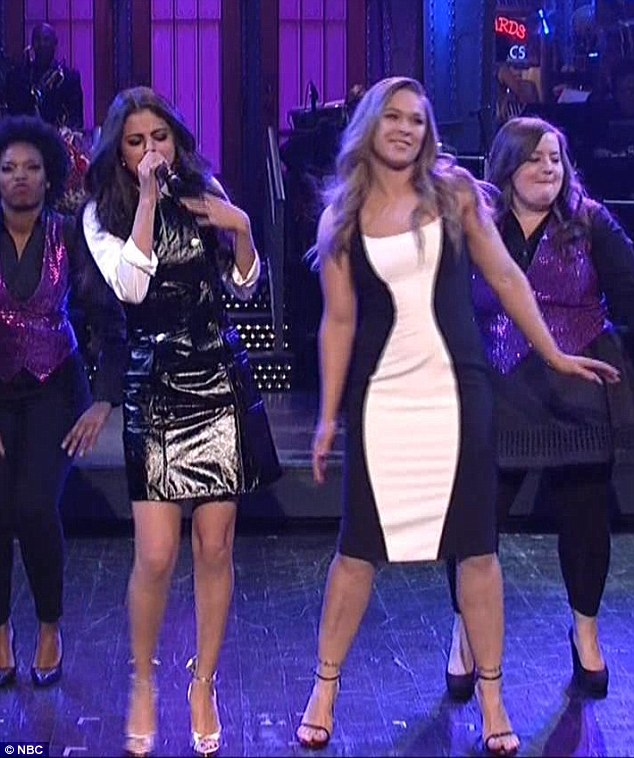 Selena Gomez black PVC drress white shirt silver shoes SNL 2016 photo NBC