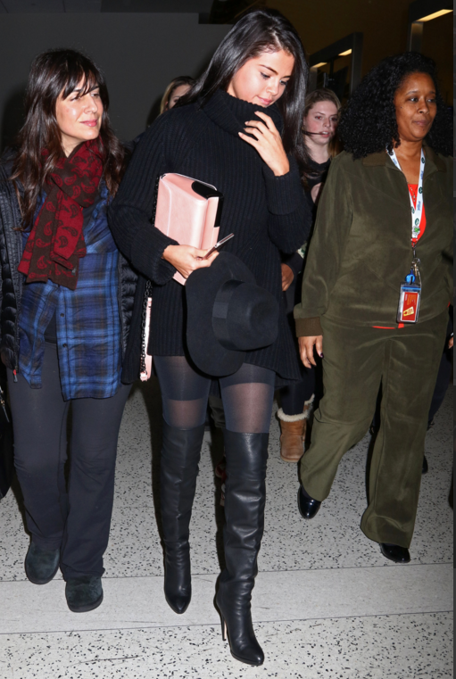 Selena gomez black sweater dress knee high boots pink bag black hat.png