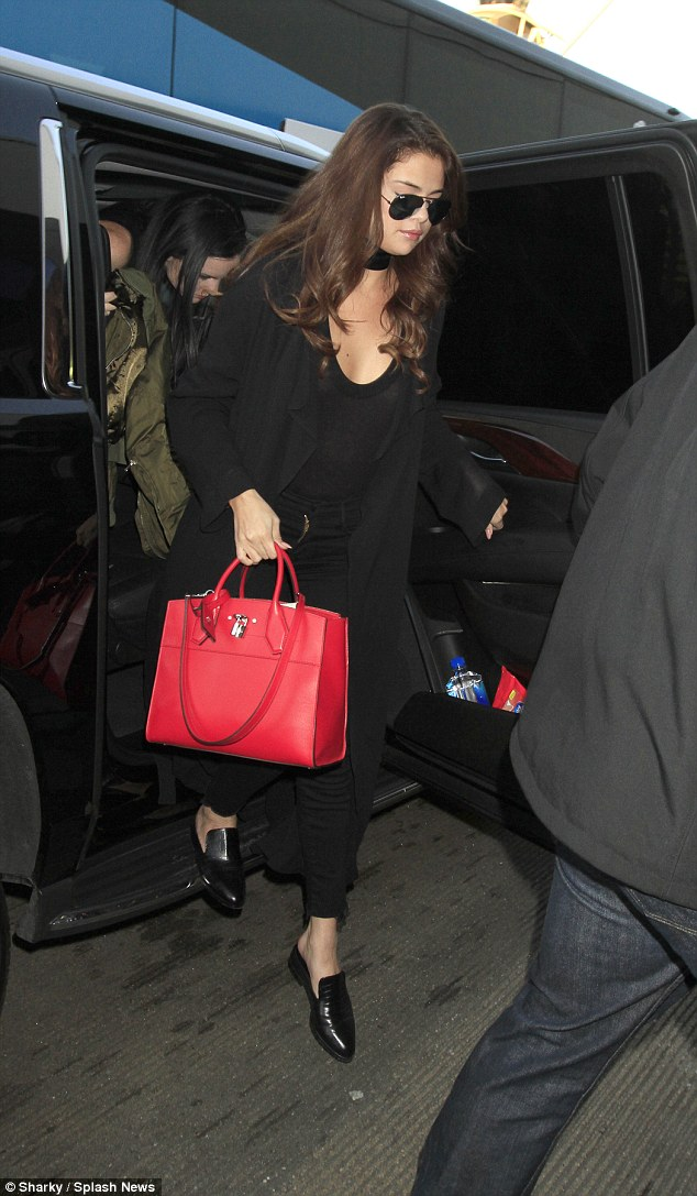 Selena gomez black ripped jeans red bag black slip on LAX photo Sharky Splash News