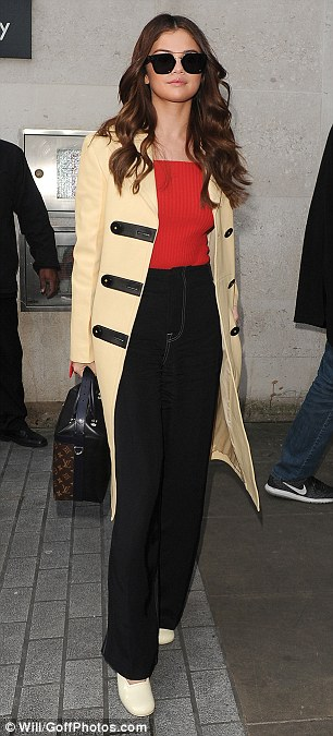 Selena Gomez cream coat red top black trousers cream shoes London 2016 photo Will Goff Photos com