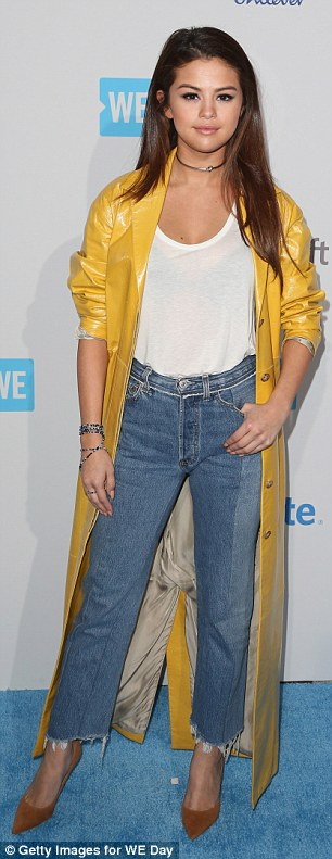 Selena Gomez yellow raincoat whie top jeans brown suede pumps WE Day 2016 photo Getty Images for WE Day