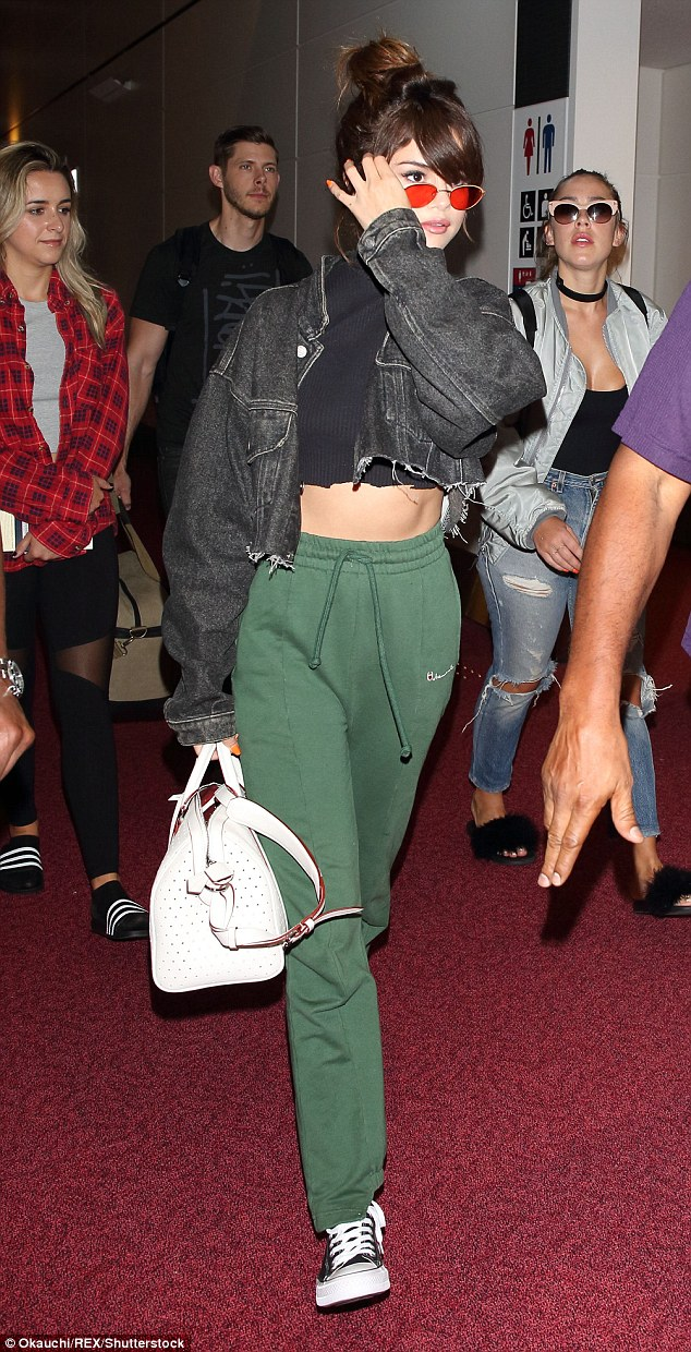 Selena Gomez cropped black polo denim jacket green joggers white bag photo Okauchi REX Shutterstock