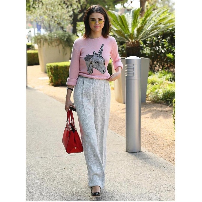 Selena Gomez pink unicorn sweater grey trousers black shoes red bag yellow sunglasses August Selena Gomez Style 2017