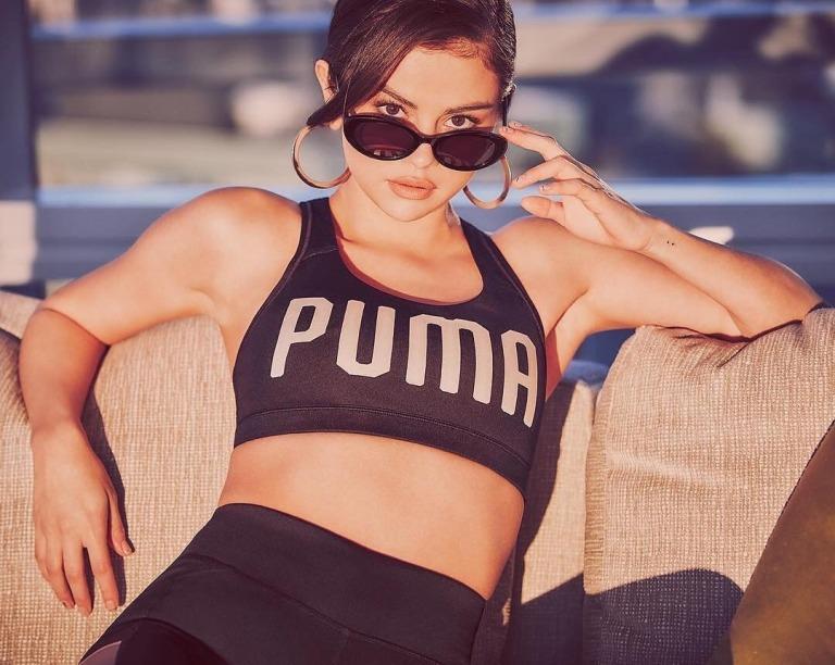 Selena Gomez black puma top black sunglasses gold hoop earrings