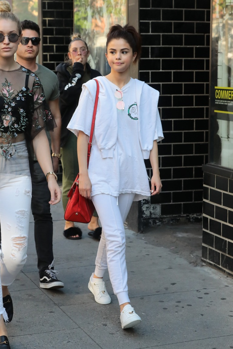 Selena Gomez white t-shirt white joggers white and gold trainers red bag green sunglasses New York September 2017 Selena Gomez street style