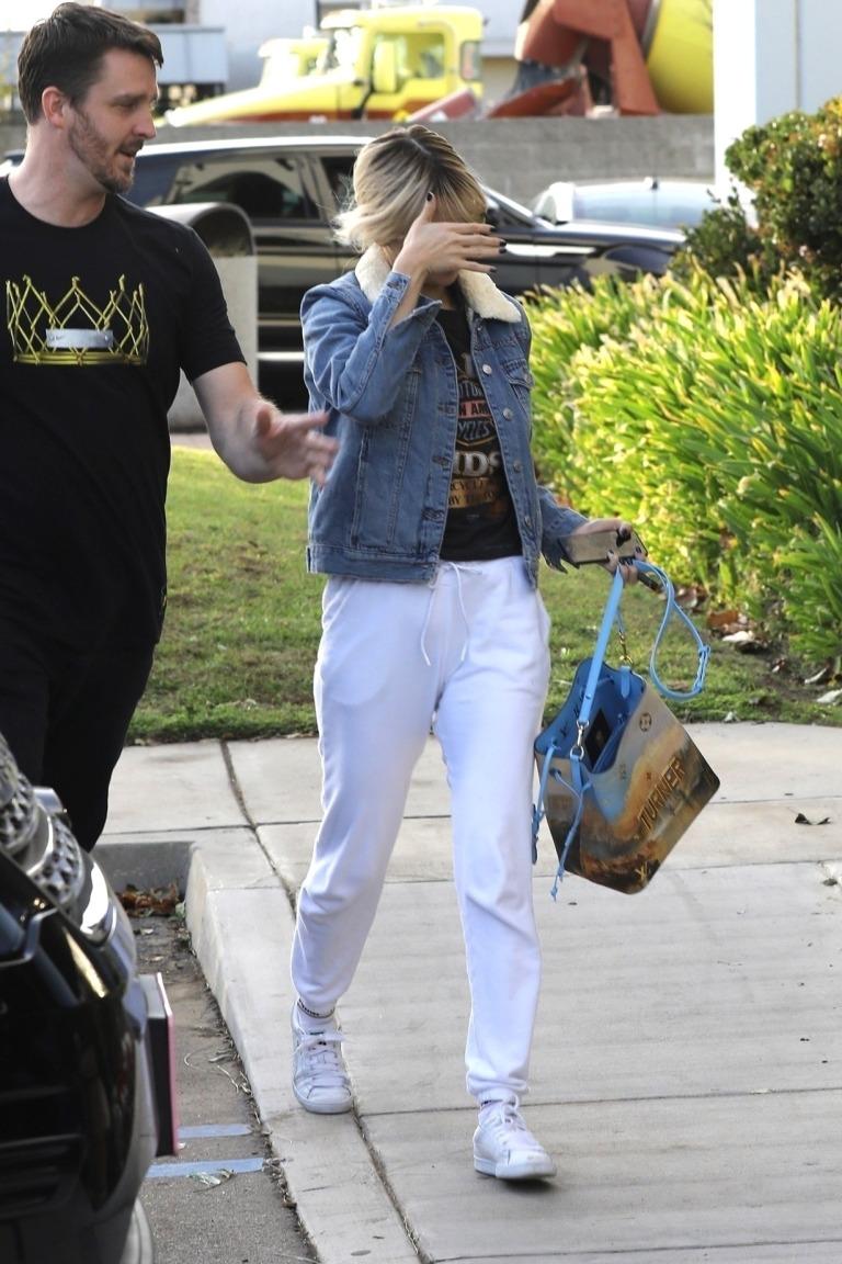 Selena Gomez style denim jacket white sneakers black Harley t-shirt blue graphic bag December 2017