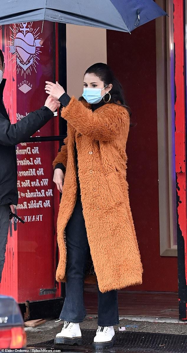 where to get Selena Gomez tan orange coat white boots Photo Elder Ordonez Spash News com